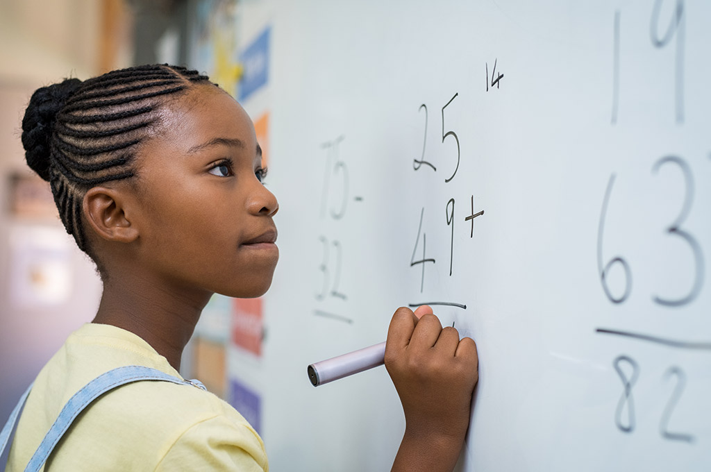 child at whiteboard doing math